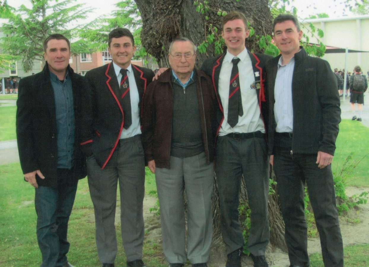 Tadeusz between  his sons and grandsons, taken under a tree, grandsons in school uniform.