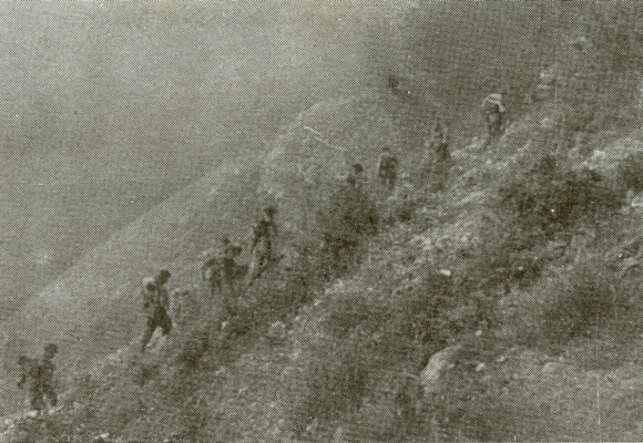 Black and white blurry photograph of Polish soldiers making their way up the slope of a mountain.