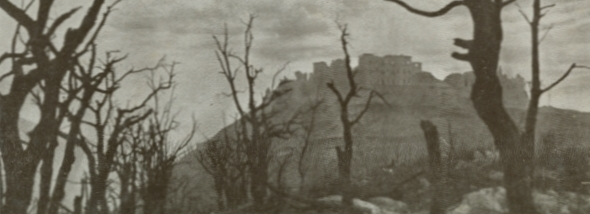 A sepia photograph of the ruins of the Monte Cassino abbey seen through stark burnt trees in the slopes below.