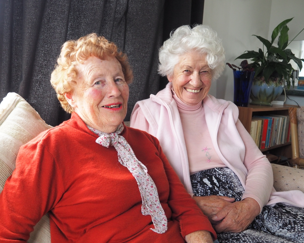 The two old ladies, smiling sweetly, sitting on a couch. Shirley has a red jersey top and a scarf to go with her red hair and Sr Martha is in baby pink jersey to go with her mop of white hair.