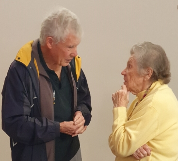White-haired Colin Smith is bending to talk to Pahiatua child Zofia Derrick wearing a pastel yellow top.