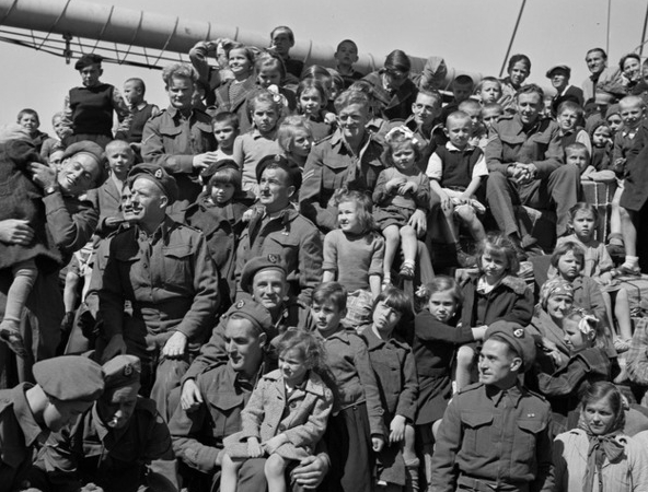 A square black and white shot of about a dozen NZ soldiers with many more children crowding around them, some in thier arms, others on their laps, mostly looking the same way - left. It seems that they could put so many into the shot because there were so many places to sit, like in an amphitheatre.