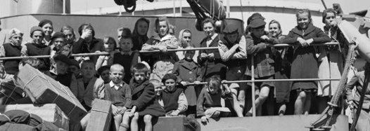 A black and white slice of children aboard the General Randall, some leaning on railings, others sitting among boxes tied with string. They are dressed in an assortment of over-sized clothing.