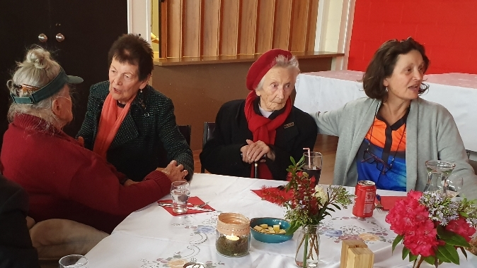Four women at a table. Joanna has her back to the camera and Marysia is talking to her. Eugenia, next to Marysia and her daughter are looking to the right. The table has flowers on it and the lunch has not yet been served.