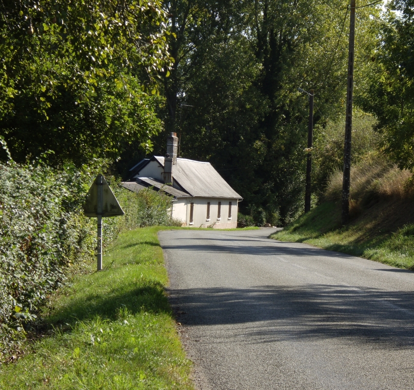 A low-roofed cottage hugging a corner in a road, tall trees in the background.