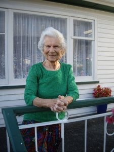Stasia Kennedy standing outside her house, leaning her arms on the balustrade of her porch. She is wearing an emerald green three-quarter sleeved top over her skirt, and is smiling.