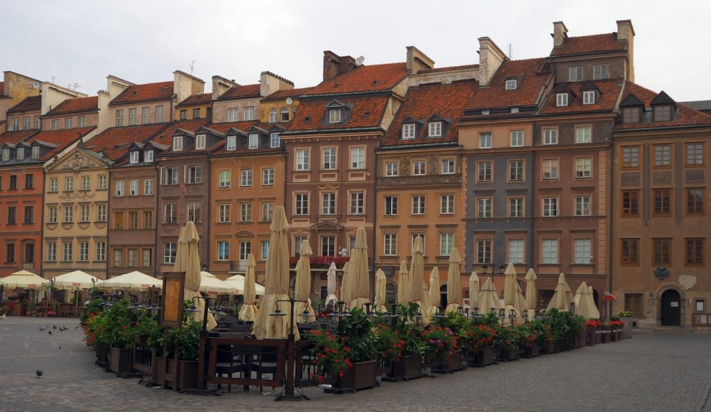 tall old buildings behind a square with umbrellas still rolled up